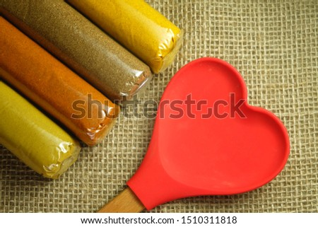 A flatlay picture of love and spices concept. Spices consist of chilli flakes, curry, India saffron, mix and coriander with heart shape wooden spoon.