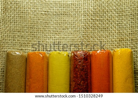 A flatlay picture variety of spices on the sackcloth. The spices are coriander, curry, mix, chilli flake, paprika and Indian Saffron.