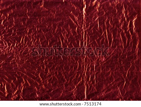 A flattened piece of red wrapping foil, suitable as a background texture.