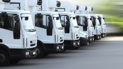 A fleet of delivery truck vehicles used to transport refrigerated goods, high dynamic, motion blurred.