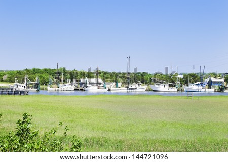 A fleet of southern fishing boats moored at their home dock on a sheltered waterway on the East coast.