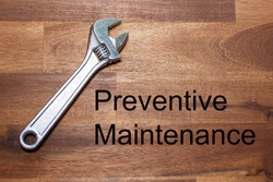 a flexible chromed adjustable wrench lies on a dark wooden table. The words Preventive Maintenance is written on the table in black letters