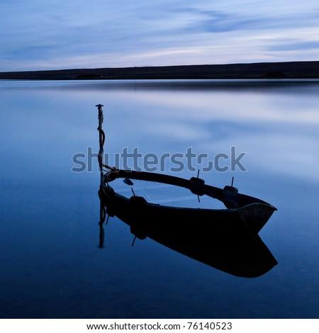A flooded boat at twilight on the Fleet Lagoon near Weymouth, Dorset, UK