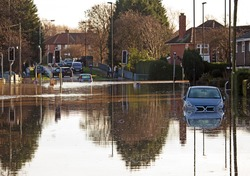 A flooded road junction with a drowned car