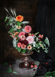A flower arrangement of dahlia and zinnias on a high wooden stand against a dark background. Floristics. Home decoration.