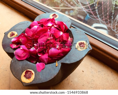 A flower petal offering to the Hindu god Shiva, with fresh pink rose petals and sandalwood paste in a wooden lotus shaped pot