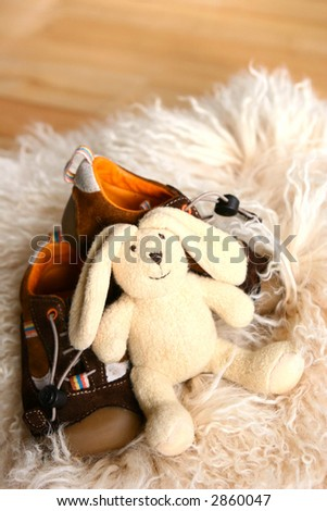 A fluffy toy bunny resting on a pair of toddler\'s shoes on sheepskin rug.