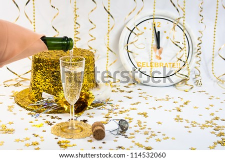 A flute of champagne and a gold glittery party hat sit in front od a clock ticking down the old year.