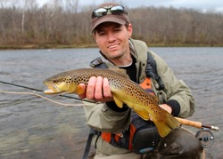 A fly fisherman posing with a Brown Trout with his fly rod and reel, before releasing the fish into the river