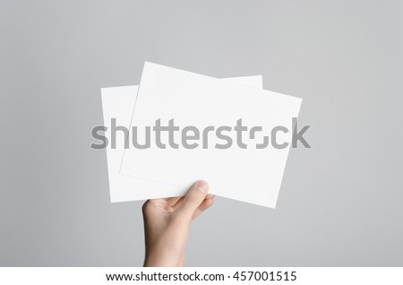 A5 Flyer / Invitation Mock-Up - Male hands holding blank flyers on a gray background. #457001515