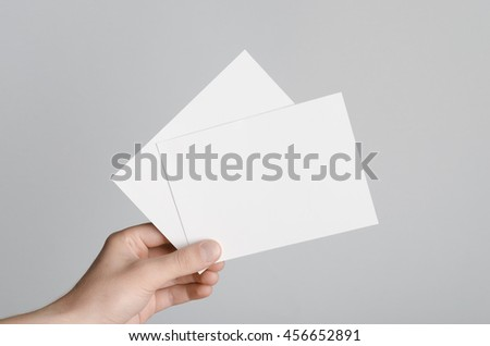 A6 Flyer / Postcard / Invitation Mock-Up - Male hands holding blank flyers on a gray background. #456652891