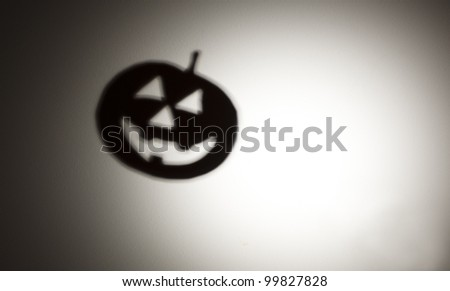 A flying halloween pumpkin shadow against an illuminated white background