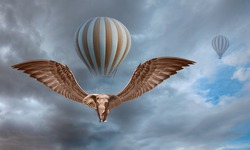 A flying winged elephant flies an hot air balloon