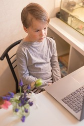 A focused smart toddler children boy is engaged in an online school at home a Neuro gymnastics lesson for brain development with a set of kinesiological exercises. The concept of distance learning