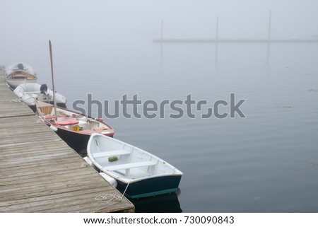 A foggy morning and calm waters with small boats docked on the Maine Coast #730090843