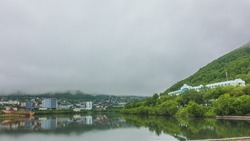 A foggy morning in the city. The houses are reflected in the mirror-smooth water of the lake. Green vegetation on the shore. The mountains are hidden in a thick mist. Petropavlovsk-Kamchatsky.
