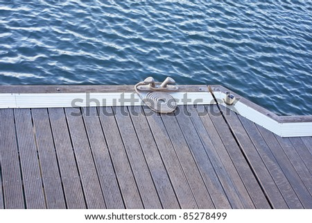 A folded spiral mooring rope with a end knot around a cleat on a wooden pier