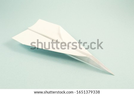 A folded white paper plane flying over a blue background. Stockfoto ©