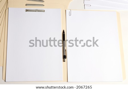 A folder lays open with blank paper on both sides. One cliped and one fastened