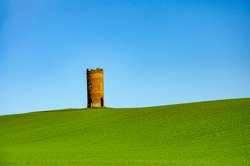 A folly, a brick built structure, stands and the distance in a green field against a vibrant blue sky