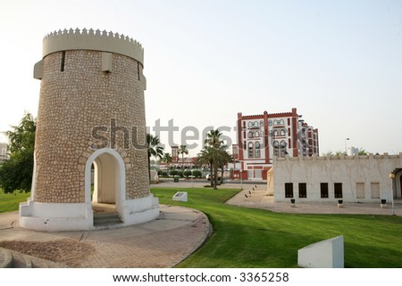 A folly in one of the parks on the Corniche in Doha, Qatar, with arabesque-style restaurants behind.