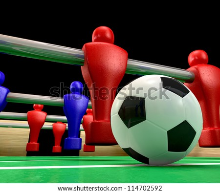A foosball table at ground level with a soccer ball being competed for by a blue and red team ready to kick off a soccer match