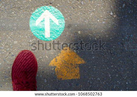 a foot and double arrowhead go forward signs on the road
