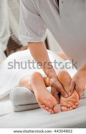 A foot massage being carried out in a spa by a masseuse