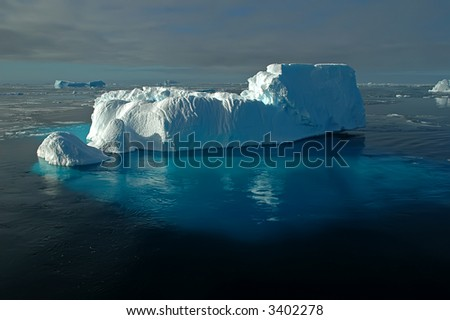 A foot-shaped iceberg swimming in front of a marvellous antarctic iceberg scenery. The huge underwater part of the iceberg is shimmering through the water surface in bright blue colours.