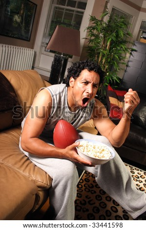 A football fan holding a bowl of popcorn yelling at the television