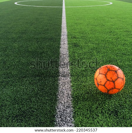 A football on artificial grasses in an indoor stadium