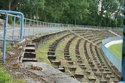 A football stadium tribune in disrepair or decayed in a provincial town in Eastern Europe. Wooden seats were removed because they were rotten and the space between rows is infested with weed.