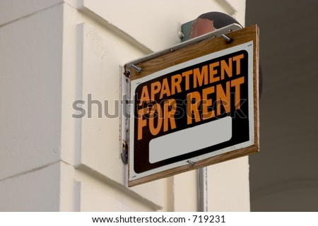 A for rent sign on display on the side of a down town apartment building.