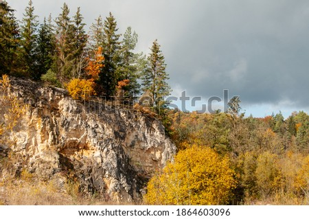 a forest in autumn leaf colors in the rocky landscape of swabian alb with a cliff of jurassic limestone Imagine de stoc ©