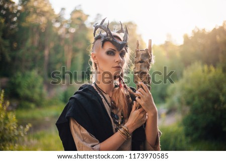 Stock Photo A forest witch with a staff in the form of a spine. Beautiful girl in the forest in a black raincoat and with a crown