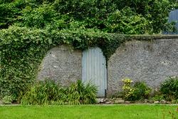 A forgotten mysterious, door to a secret garden, taken in summer.