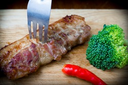 a fork on grilled pork meat steak with red chili and green broccoli on wood chopping board