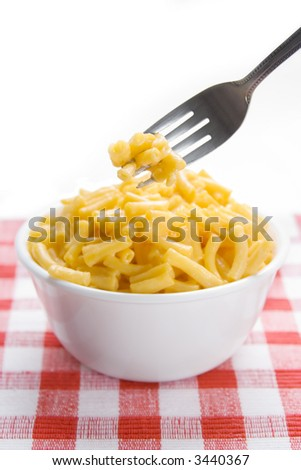 A forkful of macaroni and cheese, in front of a bowl of mac and cheese. On a red checkered placement. Selective focus, on the pasta on the fork.