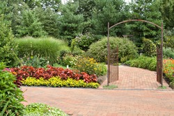 A formal garden complete with iron gate and paving brick pathway.
