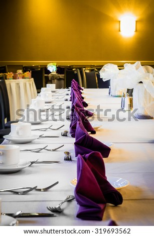 A formal Table Setting on a white tablecloth for a dinner with silverware, coffee mugs, forks, and knives.
