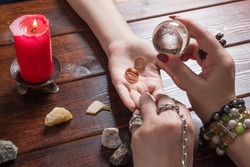 A fortune teller predicts the fate of love with wedding rings, a magic ball, lighted candles and magic stones. A Gypsy woman performs a love spell. A clairvoyant palmist reads by hand with a candle.