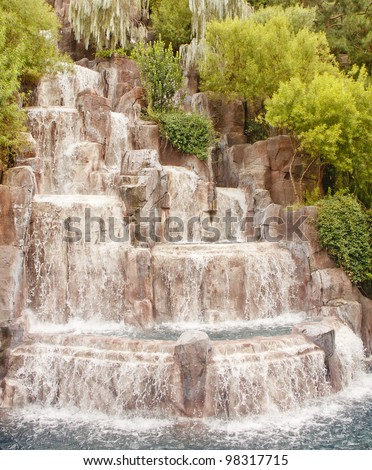 A fountain in a public garden with water flowing down rocks