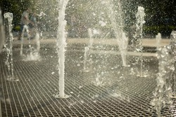 A fountain in the street. Water jets in the summer in the city. Splashing fountain on a sunny day.