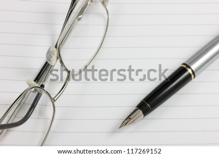A fountain pen and glasses on a lined notepad with copy space. Logos removed