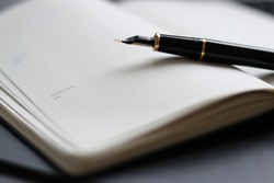 A fountain pen on top of an agenda