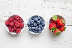A four bowls overflowing with summer berries like strawberries, raspberries, blueberries and blackberries.