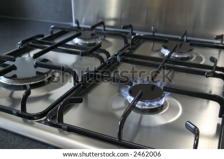 A four ring brushed steel gas hob with focus on the burning ring,