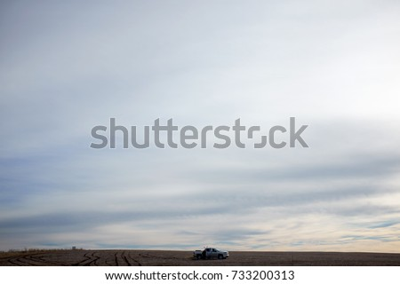 A four wheel drive car in a vast, barren desert landscape under a stormy, overcast sky.