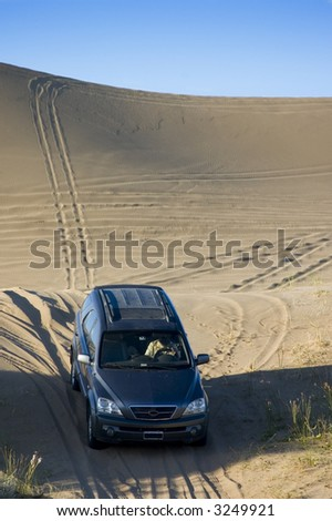 A four-wheel-drive drives through the  sand dunes.