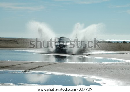 A four-wheel-drive ploughs through the water between the sand dunes.